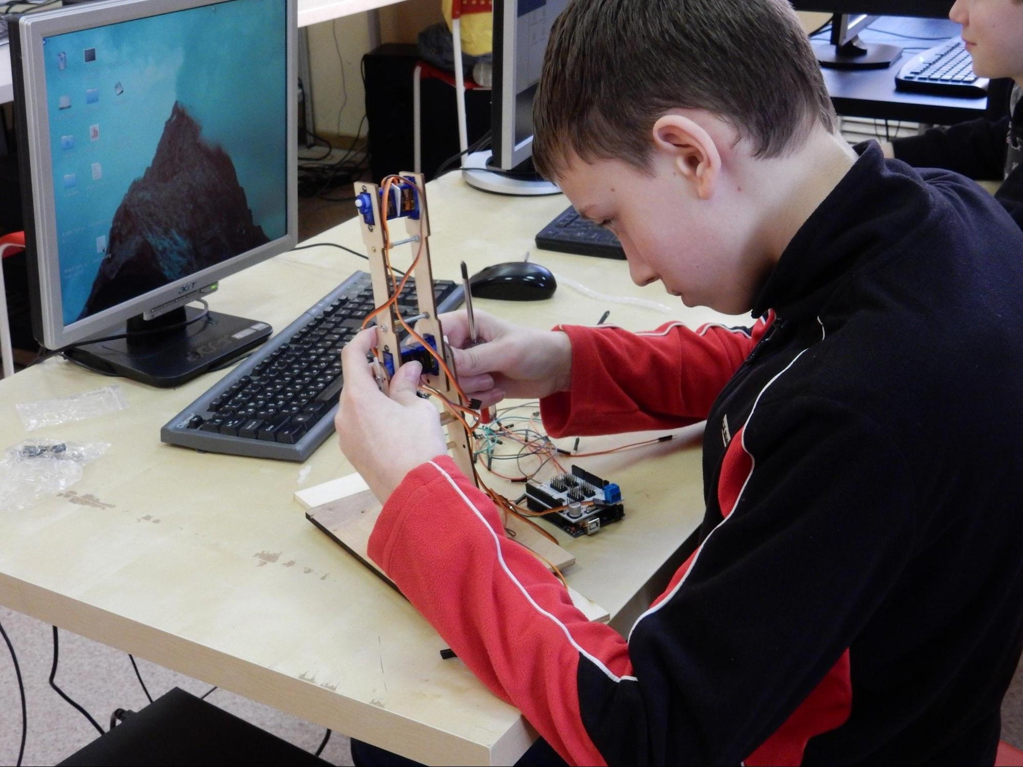 STEM образование в кружке робототехники. Ребенок играет в роботов